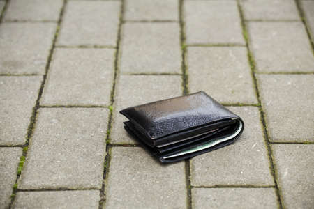 Lost black leather wallet with money lost at sidewalk