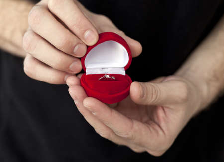 Beautiful engagement ring in red box in mans hands photo