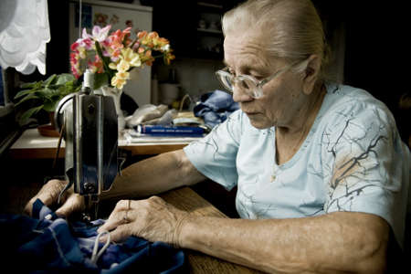 Portrait of senior woman taken during sewing on a machine photo