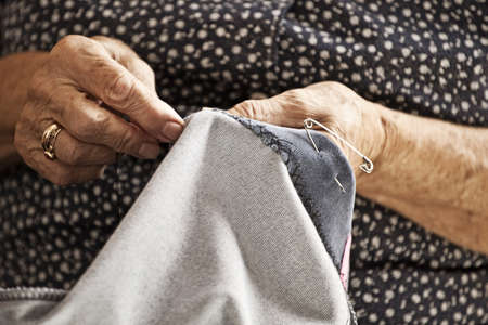 Closeup of senior womans hands taken during sewing granchildren trousers photo