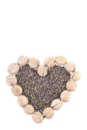 Green tea dried leaves and walnuts shaped in a heart on a wooden desk Stock Photo - 13568171