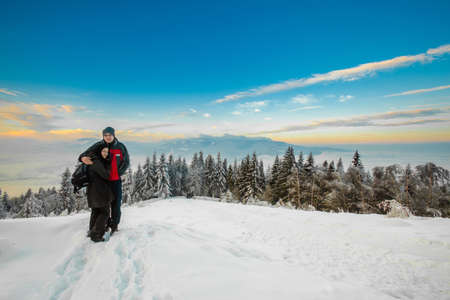 Beautiful winter sunrise portrait of young tourists, taken in polish Beskidy mountains - Rogacz hill. View on Skrzyczne mountain.