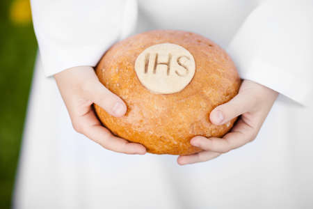 First Holy Communion concept - close up on bread in child's hands photo