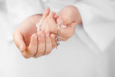 First Holy Communion concept - close up on rosary on child's hands