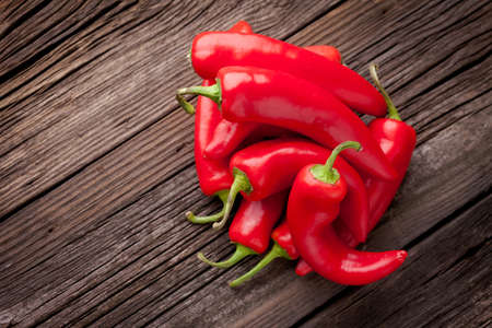 Group of fresh red hot chilli peppers on an old vintage wooden table Imagens