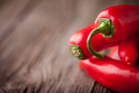 Group of fresh red hot chilli peppers on an old vintage wooden table Stock fotó