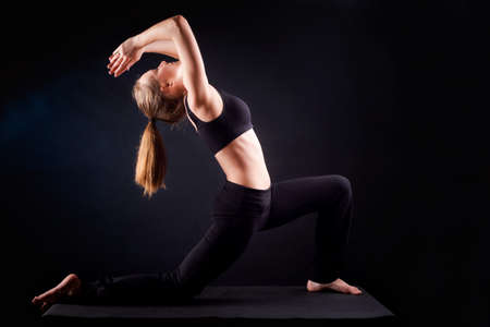 Young woman practicing yoga. Studio, black background shot. Warrior pose photo