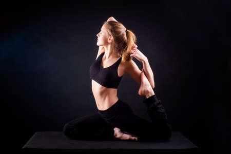 Young woman practicing yoga. Studio, black background shot