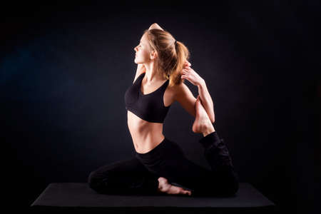 Young woman practicing yoga. Studio, black background shot
