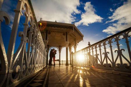 enamorados besandose: Foto rom�ntica de la pareja bes�ndose en la puesta de sol, hecho en Brighton, Inglaterra