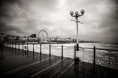 Dramatic view from Brighton pier during rainy day - black and white photo