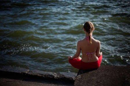 Summer outdoor yoga session in beautiful place by a lake - beautiful woman meditating photo