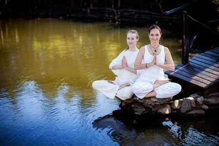 Outdoor yoga session in beautiful garden with a lake - two woman meditating photo