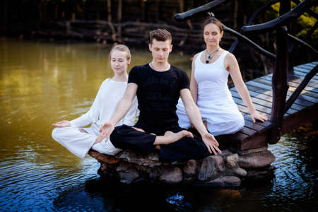 Outdoor yoga session in beautiful garden with a lake - two woman and man meditating photo