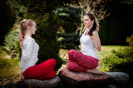 Outdoor yoga session in beautiful garden - two beautiful woman exercising photo