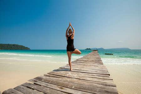 Summer yoga session on a beach - tropical Koh Rong island, Cambodia. Vriksha-asana - tree pose.