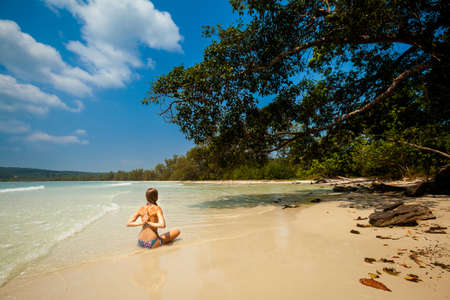 padma: Summer yoga session on a beach - tropical Koh Rong island, Cambodia. Meditation - lotus pose - padma asana