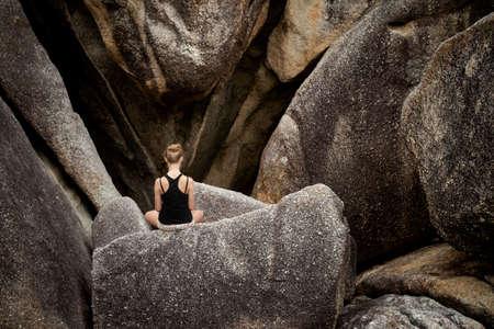 yoga: Summer yoga session on rocks - tropical Koh Samui island, Thailand. Meditation - lotus pose - padma asana Stock Photo