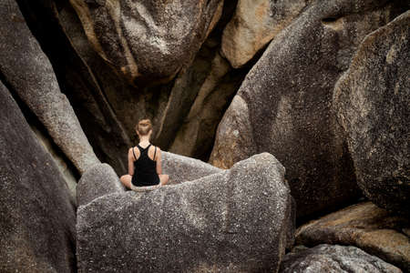 Summer yoga session on rocks - tropical Koh Samui island, Thailand. Meditation - lotus pose - padma asana Stock Photo
