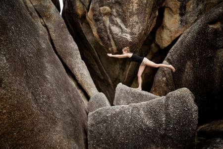 Summer yoga session on rocks - tropical Koh Samui island, Thailand. Warrior III pose, Virabhadrasana III