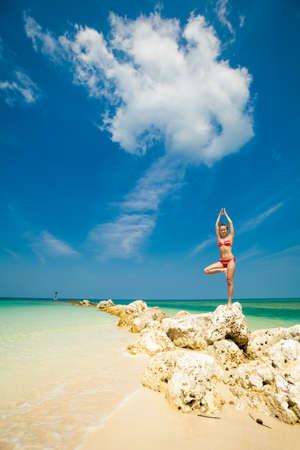 Hot summer yoga session on a beach - tropical Koh Phangan island, Thailand. Vriksha-asana - tree pose. photo