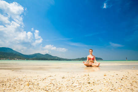 padma: Hot summer yoga session on a beach - tropical Koh Phangan island, Thailand. Meditation - lotus pose - padma asana