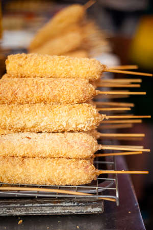 battered: Deep fried sausage skewer battered in panko flakes. Traditional thai cuisine on a market.