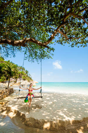 Summer seascape on tropical island Koh Phangan in Thailand - Bottle beach. Young woman on swing. photo
