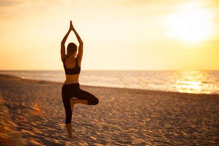 Summer yoga session on a beautiful golden beach - polish Grzybowo village, near to Kolobrzeg. Vriksha-asana - tree pose. Imagens