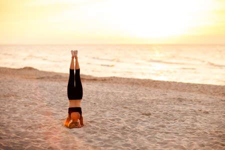 Summer yoga session on a beautiful golden beach - polish Grzybowo village, near to Kolobrzeg. Salamba Sirsasana - supported headstand