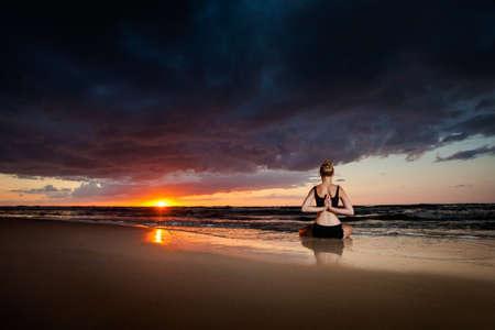 padma: Summer yoga session on a beautiful golden beach - polish Grzybowo village, near to Kolobrzeg. Meditation - lotus pose - padma asana