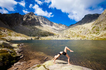 ch: Exercise yoga everywhere - in slovakian Tatry mountains. Beautiful panorama - Chata Teryho, kotlina Piatich Spišských plies