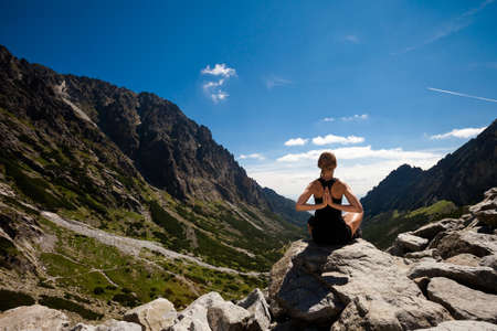 ch: Exercise yoga everywhere - in slovakian Tatry mountains. Beautiful panorama - Chata Teryho, kotlina Piatich Spišských plies - namaste in lotus pose Stock Photo
