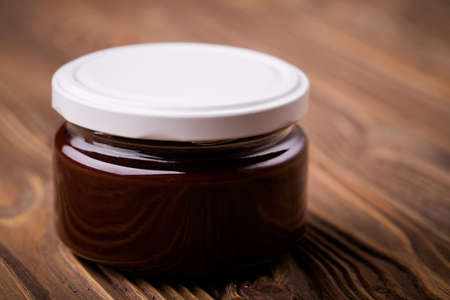 nutella: Homemade DIY natural  nutella - chocolate jam made of plums, cacao powder and vanilla. Healthy marmalade in glass jar on a wooden table Stock Photo