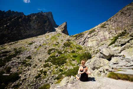 plies: Exercise yoga everywhere - in slovakian Tatry mountains. Beautiful panorama - Chata Teryho, kotlina Piatich Spisskych plies - namaste in lotus pose