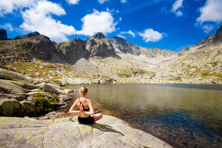 Exercise yoga everywhere - in slovakian Tatry mountains. Beautiful panorama - Chata Teryho, kotlina Piatich Spisskych plies - namaste in lotus pose