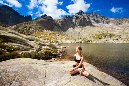 plies: Exercise yoga everywhere - in slovakian Tatry mountains. Beautiful panorama - Chata Teryho, kotlina Piatich Spisskych plies. Meditation - lotus pose - padma asana Stock Photo