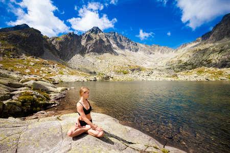 padma: Exercise yoga everywhere - in slovakian Tatry mountains. Beautiful panorama - Chata Teryho, kotlina Piatich Spisskych plies. Meditation - lotus pose - padma asana Stock Photo