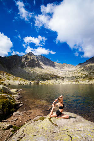 plies: Exercise yoga everywhere - in slovakian Tatry mountains. Beautiful panorama - Chata Teryho, kotlina Piatich Spisskych plies. Eka Pada Rajakapotasana - mermaid pose