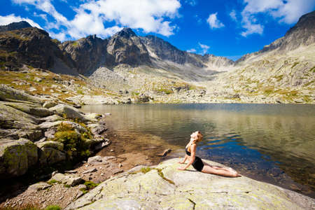 plies: Exercise yoga everywhere - in slovakian Tatry mountains. Beautiful panorama - Chata Teryho, kotlina Piatich Spisskych plies. Naga-asana, cobra pose Stock Photo