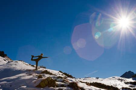 eka: Yoga session in beautiful slovakian Belianske Tatry mountains. Beautiful sunny panorama - Siroka dolina - wide valley in snow - Standing Eka Pada Rajakapotasana, mermaid pose