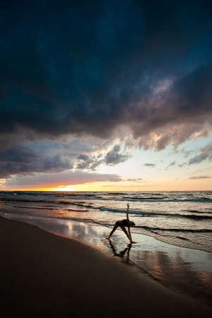 trikonasana: Summer yoga session on a beautiful golden beach - polish Grzybowo village, near to Kolobrzeg. trikonasana - triangle pose.