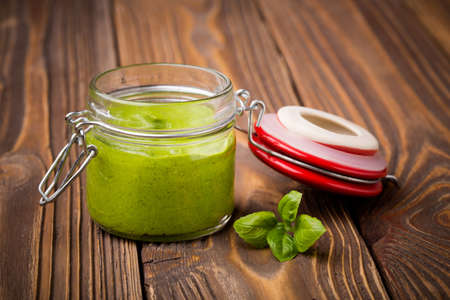 'baby spinach': Natural homemade DIY vegan very healthy green pesto made of baby spinach and pini nuts in a glass jar on a wooden table
