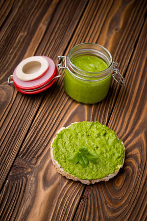 baby rice: Natural homemade DIY vegan very healthy green pesto made of baby spinach and pini nuts in a glass jar on a wooden table with rice waffle