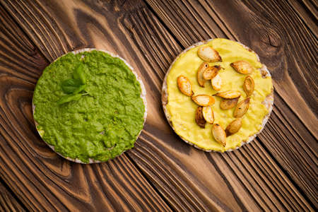 baby spinach: Homemade DIY natural healthy pumpkin feta paste and baby spinach pesto on a wooden table with  rice waffle