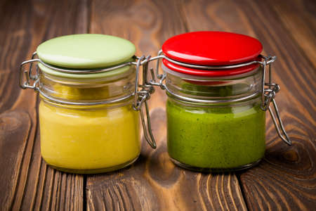 baby spinach: Homemade DIY natural healthy pumpkin feta paste and baby spinach pesto in a glass jar on a wooden table