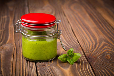baby spinach: Natural homemade DIY vegan very healthy green pesto made of baby spinach and pini nuts in a glass jar on a wooden table