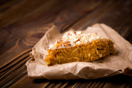 Homemade DIY natural pumpkin cake made with nuts and white chocolate on a wooden table