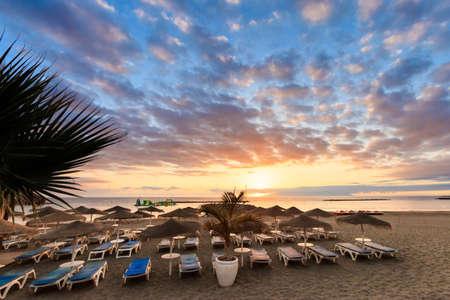 adeje: Summer sunset seascape on tropical island Tenerife, Canary in Spain. Costa Adeje view on La Gomera island from playa Fanabe beach.