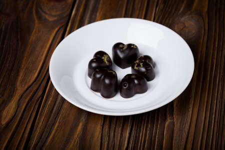 pralines: Homemade DIY natural vegan healthy heart-shaped  chocolate pralines with matcha green tea made of coconut oil, cacao, carob, sugar on a white plate and wooden table